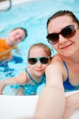 foto of swimming pool family  - Happy family mother and her kids at outdoors swimming pool taking selfie on tropical vacation - JPG