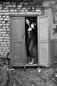 image of ax  - frightened woman stands in meter cabinets with an ax in his hand - JPG