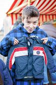 picture of thrift store  - funny teenage boy on a flea market is trying too small dresses - JPG