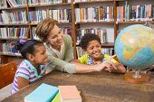 pic of pupils  - Pupils and teacher looking at globe in library at elementary school - JPG