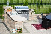 picture of angle  - High angle view of a stylish outdoor kitchen on a brick patio with a built in gas barbecuerug and dining table overlooking a green lawn and railing - JPG