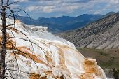 picture of mammoth  - The amazing Mammoth Hot Springs in Yellowstone National Park with steam rising from the colorful staircase formation distant high mountains and a fluffy cloud sky - JPG