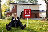picture of house representatives  - Exhausted estate agent sitting outside the house