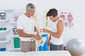 stock photo of herniated disc  - Doctor showing anatomical spine to his patient in medical office - JPG