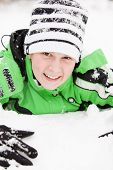 stock photo of beanie hat  - Friendly happy young boy with a charming smile playing in winter snow lying on his stomach looking up at the camera in a knitted beanie hat and warm green jacket - JPG