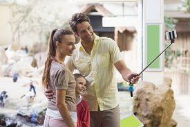 stock photo of zoo  - Happy family using a selfie stick at the zoo - JPG