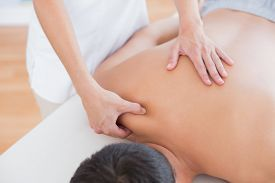 picture of physiotherapist  - Physiotherapist doing shoulder massage to her patient in medical office - JPG