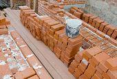 stock photo of mason  - Mason bricklaying background with bucket of clay brick blocks - JPG