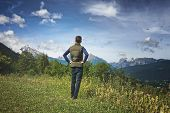 stock photo of bavarian alps  - Rear view of a male tourist standing on a grassy plateau enjoying the scenic Bavarian alps in the Berchtesgaden National Park - JPG