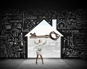 image of keyhole  - Young businesswoman and keyhole at background lifting big key above head - JPG