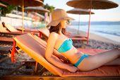 picture of sunbathing woman  - Beautiful woman sunbathing in a bikini on a beach at tropical travel resort - JPG