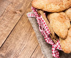 image of bakeshop  - Freshly baked grain bread with sesame in a wicker basket on burlap napkin - JPG