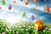 stock photo of easter candy  - Colorful Easter eggs falling down on a flower field - JPG