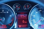 Speedometer, rev counter, fuel and temperature gauge of a sports car dashboard