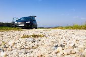 Black Van Parked On Gravel Road, Low Angle, Copyspace, Trunk And Door Open, Nobody, Offroad, Camping poster