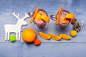 Glasses With Mulled Wine Or Hot Drink Near Wooden Deer Decoration On Blue Wooden Background. Mulled  poster