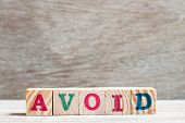 Letter Block In Word Avoid On Wood Background poster