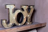 Wooden Letters Forming Word Joy Written On Grey Wall.christmas Postcard. The Inscription: Joy To The poster