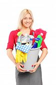Female cleaner holding a bucket with cleaning supplies isolated on white background
