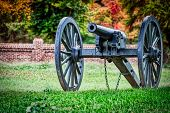 A Cannon Sitting From The American Civil War Sits On A Virginia Field. With A Fall Forest In The Bac poster