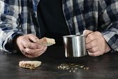 Poor Elderly Man With Piece Of Bread And Metal Mug At Table, Closeup poster