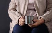 Poor Elderly Woman Holding Metal Mug On Dark Background, Closeup poster
