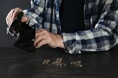Poor Elderly Man Counting Coins At Table, Focus On Hands poster
