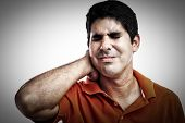 stock photo of young men  - Stressed hispanic man suffering from pain in his neck and back - JPG