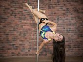Girl Training Pole Dance Hanging Upside Down And Smiling In A Studio poster