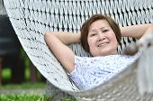 Senior Woman Relaxing And Smiling On Hammock, Summer Garden With Hanging Hammock For Relaxation On L poster