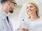 Young Dentist Talks With Patient In Dental Clinic. poster