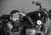 Bikers Lifestyle Concept. Man With Beard, Biker In Leather Jacket Near Motor Bike In Garage, Brick W poster
