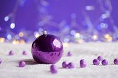 Purple Christmas Ball And Beads On White Knitted Fabric On Purple Background With Warm Bokeh. New Ye poster