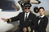 image of cabin crew  - Two happy cabin crew members standing together by an airplane at airfield - JPG