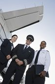 image of cabin crew  - Low angle view of three multiethnic cabin crew members standing together against airplane wing at airfield - JPG