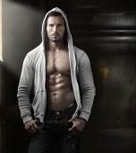 image of hairy  - Young handsome macho man with open jacket revealing muscular chest and abs in industrial garage with window light - JPG