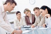 image of business meetings  - Businessman leaning on desk explaining to four colleagues sitting - JPG