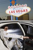 Elvis impersonator in the car in front of a 'Welcome to Las Vegas' sign