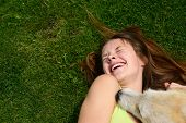stock photo of tickle  - beautiful young happy laugh girl playing with her dog outdoor - JPG