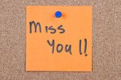 stock photo of miss you  - sticky note orange with miss you message on cork - JPG