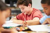 stock photo of 11 year old  - Pupils Studying At Desks In Classroom - JPG