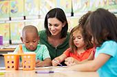 stock photo of teachers  - Group Of Elementary Age Children In Art Class With Teacher - JPG