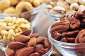 image of mixed nut  - Many glass bowls of almonds walnuts pistachios and pine nuts