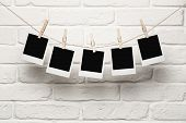 picture of reminder  - Blank photos hanging on a clothesline over brick wall background with copy space - JPG
