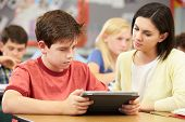 image of 11 year old  - Pupils In Class Using Digital Tablet With Teacher - JPG