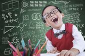 foto of preschool  - Boy student is laughing in class while drawing something - JPG