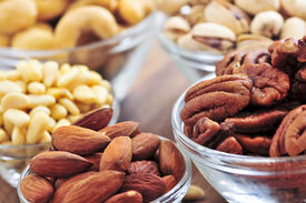 image of mixed nut  - Many glass bowls of almonds walnuts pistachios and pine nuts  - JPG