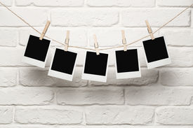 stock photo of clotheslines  - Blank photos hanging on a clothesline over brick wall background with copy space - JPG