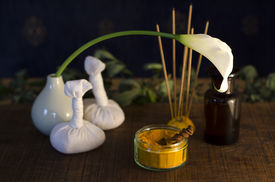 image of vedic  - A table top arrangement of spice oil and massaging tools used in Ayurveda massage.