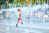 foto of water jet  - excited boy running between water flow in city park - JPG